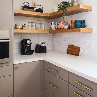 ロサンゼルスの巨大な北欧スタイルのおしゃれなキッチン (アンダーカウンターシンク、フラットパネル扉のキャビネット、グレーのキャビネット、クオーツストーンカウンター、白いキッチンパネル、サブウェイタイルのキッチンパネル、シルバーの調理設備、竹フローリング、黄色い床、白いキッチンカウンター) の写真