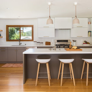 Inspiration for a scandinavian l-shaped kitchen in Los Angeles with an undermount sink, flat-panel cabinets, grey cabinets, quartz benchtops, white splashback, stainless steel appliances, bamboo floors, a peninsula and white benchtop.