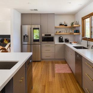 Idee per un'ampia cucina nordica con lavello sottopiano, ante lisce, ante grigie, top in quarzo composito, paraspruzzi bianco, paraspruzzi con piastrelle diamantate, elettrodomestici in acciaio inossidabile, pavimento in bambù, penisola, pavimento giallo e top bianco