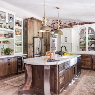 サクラメントの中サイズのトラディショナルスタイルのおしゃれなキッチン (エプロンフロントシンク、シェーカースタイル扉のキャビネット、中間色木目調キャビネット、クオーツストーンカウンター、カラー調理設備、クッションフロア、茶色い床、白いキッチンカウンター) の写真
