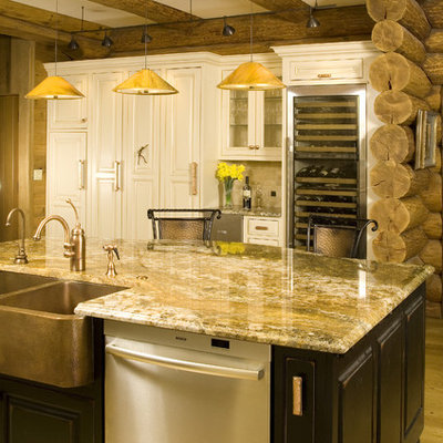 Example of a mid-sized mountain style l-shaped light wood floor open concept kitchen design in Seattle with a farmhouse sink, raised-panel cabinets, white cabinets, stainless steel appliances, granite countertops, beige backsplash and an island