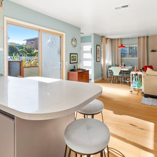 This is an example of a midcentury kitchen in San Francisco with an undermount sink, flat-panel cabinets, quartz benchtops, blue splashback, subway tile splashback, stainless steel appliances, vinyl floors and white benchtop.