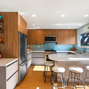 Photo of a midcentury u-shaped kitchen in Other with a double-bowl sink, flat-panel cabinets, medium wood cabinets, blue splashback, stainless steel appliances, medium hardwood flooring, a breakfast bar and white worktops.