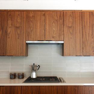 デトロイトの中サイズのミッドセンチュリースタイルのおしゃれなキッチン (ドロップインシンク、フラットパネル扉のキャビネット、中間色木目調キャビネット、珪岩カウンター、グレーのキッチンパネル、セラミックタイルのキッチンパネル、シルバーの調理設備の、無垢フローリング、オレンジの床、ベージュのキッチンカウンター) の写真