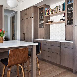Idéer för avskilda, mellanstora 50 tals vitt l-kök, med en undermonterad diskho, släta luckor, skåp i mellenmörkt trä, bänkskiva i kvarts, vitt stänkskydd, stänkskydd i marmor, svarta vitvaror, ljust trägolv, en köksö och brunt golv