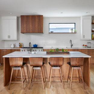 デンバーの広い北欧スタイルのおしゃれなキッチン (アンダーカウンターシンク、フラットパネル扉のキャビネット、中間色木目調キャビネット、珪岩カウンター、白いキッチンパネル、セラミックタイルのキッチンパネル、シルバーの調理設備、淡色無垢フローリング、白いキッチンカウンター) の写真