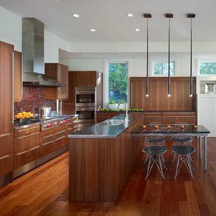 Ejemplo de cocina minimalista con encimera de acero inoxidable, salpicadero rojo, salpicadero con mosaicos de azulejos, suelo de madera en tonos medios y una isla