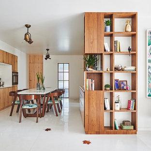 Ejemplo de cocina de galera, exótica, con armarios con paneles lisos, puertas de armario de madera oscura, electrodomésticos de acero inoxidable, una isla, suelo blanco y encimeras blancas