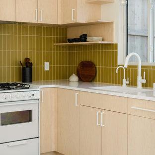 ロサンゼルスの小さい北欧スタイルのおしゃれなL型キッチン (黄色いキッチンパネル、セラミックタイルのキッチンパネル、白い調理設備、コンクリートの床、アイランドなし、白いキッチンカウンター、アンダーカウンターシンク、フラットパネル扉のキャビネット、淡色木目調キャビネット、グレーの床) の写真