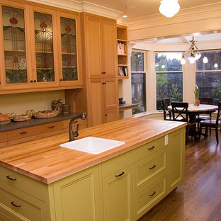 Contemporary eat-in kitchen appliance - Example of a trendy eat-in kitchen design in Seattle with recessed-panel cabinets, wood countertops, a drop-in sink and green cabinets