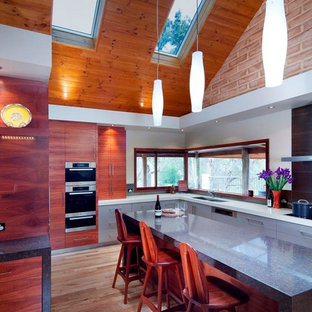 Design ideas for a large contemporary l-shaped kitchen pantry in Perth with a submerged sink, flat-panel cabinets, medium wood cabinets, engineered stone countertops, porcelain splashback, stainless steel appliances, light hardwood flooring and an island.