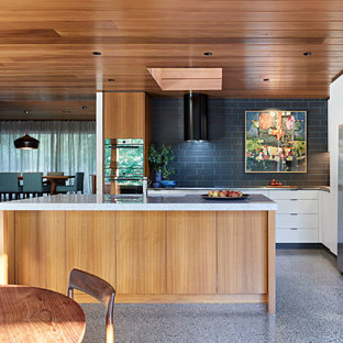 Photo of a mid-sized midcentury l-shaped eat-in kitchen in Melbourne with an undermount sink, flat-panel cabinets, medium wood cabinets, marble benchtops, black splashback, porcelain splashback, concrete floors, with island, grey floor, stainless steel appliances and grey benchtop.