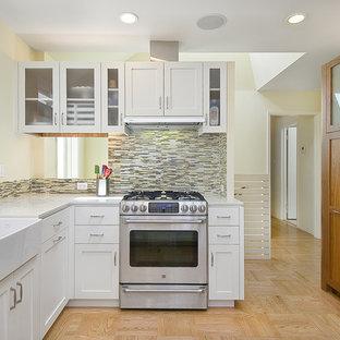 Неиссякаемый источник вдохновения для домашнего уюта: кухня в современном стиле с техникой из нержавеющей стали, раковиной в стиле кантри, белыми фасадами, фартуком из удлиненной плитки и разноцветным фартуком