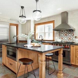 ポートランドの中サイズのカントリー風おしゃれなキッチン (エプロンフロントシンク、シェーカースタイル扉のキャビネット、中間色木目調キャビネット、御影石カウンター、白いキッチンパネル、セラミックタイルのキッチンパネル、シルバーの調理設備の、スレートの床、マルチカラーの床、黒いキッチンカウンター) の写真