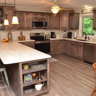 他の地域の大きいカントリー風おしゃれなキッチン (アンダーカウンターシンク、レイズドパネル扉のキャビネット、茶色いキャビネット、人工大理石カウンター、シルバーの調理設備の、ベージュのキッチンカウンター) の写真