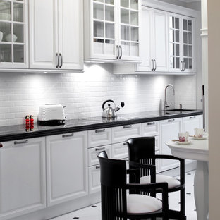 Traditional eat-in kitchen designs - Elegant galley white floor eat-in kitchen photo in Other with an undermount sink, glass-front cabinets, white cabinets, granite countertops, white backsplash, porcelain backsplash and stainless steel appliances