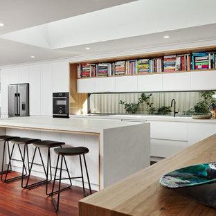 Пример оригинального дизайна: большая угловая кухня в современном стиле с обеденным столом, врезной раковиной, плоскими фасадами, белыми фасадами, столешницей из кварцевого агломерата, фартуком с окном, черной техникой, темным паркетным полом, островом, коричневым полом и белой столешницей
