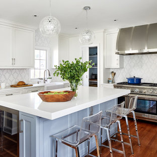 Mid-sized transitional u-shaped medium tone wood floor and brown floor eat-in kitchen photo in DC Metro with a farmhouse sink, recessed-panel cabinets, blue cabinets, quartz countertops, white backsplash, marble backsplash, paneled appliances, an island and white countertops