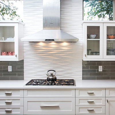 Mid-sized trendy l-shaped open concept kitchen photo in Denver with white cabinets, quartz countertops, gray backsplash, glass tile backsplash, stainless steel appliances, an undermount sink, recessed-panel cabinets and an island