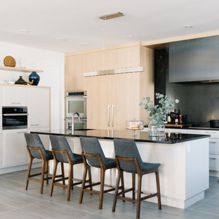 Photo of a large contemporary u-shaped eat-in kitchen in Edmonton with flat-panel cabinets, white cabinets, quartz benchtops, black splashback, stone slab splashback, panelled appliances, porcelain floors, with island, grey floor and black benchtop.