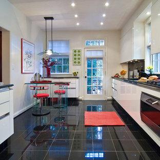 Idee per una cucina minimalista di medie dimensioni con ante lisce, ante bianche, lavello sottopiano, paraspruzzi nero, paraspruzzi in lastra di pietra, elettrodomestici in acciaio inossidabile, pavimento in marmo, pavimento nero, isola, top in granito e top nero