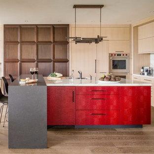 Diseño de cocina actual, de tamaño medio, con fregadero bajoencimera, armarios con paneles lisos, puertas de armario rojas, encimera de mármol, salpicadero blanco, salpicadero de mármol, electrodomésticos de acero inoxidable, suelo de madera clara, dos o más islas y suelo beige