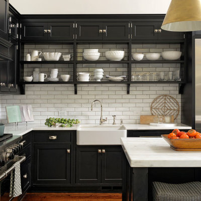 Eat-in kitchen - large transitional l-shaped medium tone wood floor and brown floor eat-in kitchen idea in DC Metro with a farmhouse sink, beaded inset cabinets, black cabinets, white backsplash, subway tile backsplash, stainless steel appliances, an island and quartzite countertops