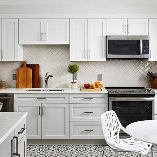 Inredning av ett klassiskt vit vitt kök och matrum, med en dubbel diskho, skåp i shakerstil, vita skåp, beige stänkskydd, rostfria vitvaror, flerfärgat golv och vinylgolv