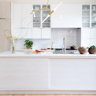 This is an example of a mid-sized midcentury single-wall kitchen pantry in DC Metro with an undermount sink, shaker cabinets, white cabinets, marble benchtops, white splashback, marble splashback, stainless steel appliances, light hardwood floors, with island, brown floor and white benchtop.