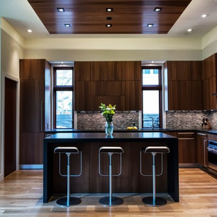 Example of a large trendy l-shaped light wood floor open concept kitchen design in DC Metro with flat-panel cabinets, dark wood cabinets, brown backsplash, mosaic tile backsplash, quartz countertops and stainless steel appliances