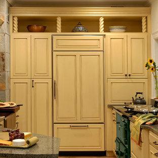 Idéer för att renovera ett mellanstort vintage kök, med en halv köksö, luckor med profilerade fronter, gula skåp, granitbänkskiva, en rustik diskho, grått stänkskydd, stänkskydd i stenkakel, integrerade vitvaror, klinkergolv i terrakotta och beiget golv