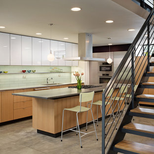 Midcentury u-shaped eat-in kitchen in Seattle with a drop-in sink, flat-panel cabinets, medium wood cabinets, soapstone benchtops, glass tile splashback and stainless steel appliances.