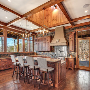 Inspiration for a country l-shaped kitchen in Other with raised-panel cabinets, medium wood cabinets, metallic splashback, stainless steel appliances, medium hardwood floors, with island and brown benchtop.