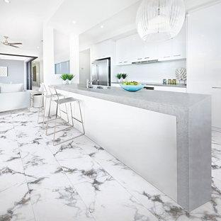ボルチモアの中くらいの北欧スタイルのおしゃれなキッチン (ドロップインシンク、フラットパネル扉のキャビネット、白いキャビネット、コンクリートカウンター、白いキッチンパネル、セラミックタイルのキッチンパネル、シルバーの調理設備、クッションフロア、白い床、グレーのキッチンカウンター) の写真