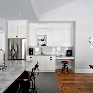 Diseño de cocina actual con electrodomésticos de acero inoxidable, encimera de granito, armarios estilo shaker, puertas de armario blancas y salpicadero blanco
