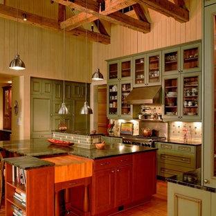 チャールストンの大きいエクレクティックスタイルのおしゃれなキッチン (ガラス扉のキャビネット、緑のキャビネット、ベージュキッチンパネル、シルバーの調理設備の、無垢フローリング) の写真