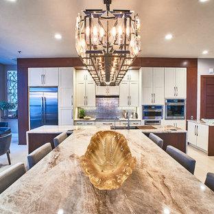 Große Moderne Wohnküche mit Unterbauwaschbecken, Schrankfronten im Shaker-Stil, weißen Schränken, Küchenrückwand in Metallic, Küchengeräten aus Edelstahl, beigem Boden, Quarzit-Arbeitsplatte, Rückwand aus Glasfliesen, Kalkstein und zwei Kücheninseln in Baltimore