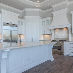 Photo of an expansive traditional kitchen pantry in Miami with a submerged sink, raised-panel cabinets, white cabinets, stainless steel appliances, ceramic flooring and an island.