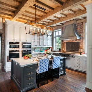 Large eclectic eat-in kitchen ideas - Inspiration for a large eclectic u-shaped medium tone wood floor and brown floor eat-in kitchen remodel in Other with glass-front cabinets, an island, a drop-in sink, white cabinets, marble countertops, multicolored backsplash, ceramic backsplash and stainless steel appliances
