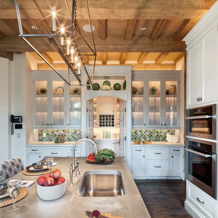 Large eclectic kitchen pantry photos - Large eclectic u-shaped medium tone wood floor and brown floor kitchen pantry photo in Other with glass-front cabinets, an island, a drop-in sink, white cabinets, marble countertops, multicolored backsplash, ceramic backsplash and stainless steel appliances