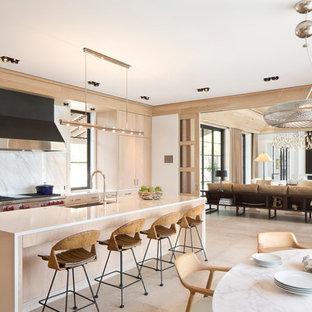 Foto de cocina comedor tropical, grande, con armarios con paneles lisos, puertas de armario de madera clara, salpicadero blanco, salpicadero de losas de piedra, electrodomésticos con paneles y una isla