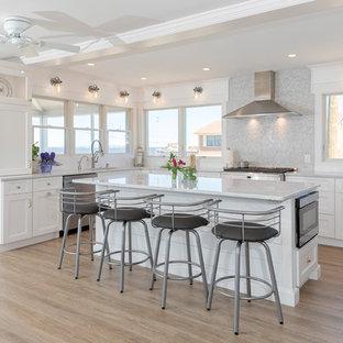 Idéer för mellanstora maritima vitt kök, med en undermonterad diskho, skåp i shakerstil, vita skåp, bänkskiva i kvartsit, grått stänkskydd, stänkskydd i marmor, rostfria vitvaror, målat trägolv, en köksö och brunt golv