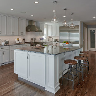 Design ideas for a large arts and crafts single-wall eat-in kitchen in Seattle with a drop-in sink, shaker cabinets, white cabinets, white splashback, ceramic splashback, stainless steel appliances, dark hardwood floors, with island, granite benchtops, brown floor and grey benchtop.