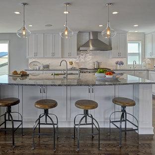 シアトルの大きいおしゃれなキッチン (ドロップインシンク、シェーカースタイル扉のキャビネット、白いキャビネット、白いキッチンパネル、セラミックタイルのキッチンパネル、シルバーの調理設備の、濃色無垢フローリング、御影石カウンター、茶色い床、グレーのキッチンカウンター) の写真