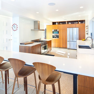 Inspiration for a midcentury modern u-shaped kitchen remodel in Seattle with a double-bowl sink, flat-panel cabinets, medium tone wood cabinets, white backsplash, glass sheet backsplash and stainless steel appliances