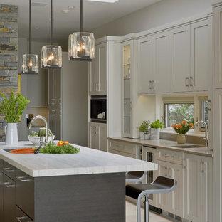 Inspiration pour une cuisine parallèle design fermée et de taille moyenne avec un évier encastré, un placard à porte shaker, des portes de placard beiges, une crédence beige, un électroménager en acier inoxydable, un sol en carrelage de porcelaine et un îlot central.
