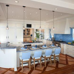 Imagen de cocina en U, costera, abierta, con armarios con paneles empotrados, puertas de armario beige, salpicadero azul, salpicadero de azulejos tipo metro, electrodomésticos con paneles y encimeras azules
