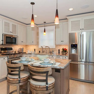 This is an example of a small beach style l-shaped open plan kitchen in Seattle with an undermount sink, louvered cabinets, white cabinets, granite benchtops, beige splashback, stone tile splashback, stainless steel appliances, porcelain floors and with island.