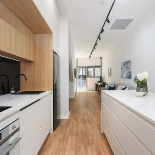 This is an example of a contemporary galley kitchen in Sydney with a drop-in sink, flat-panel cabinets, white cabinets, black splashback, glass sheet splashback, black appliances, medium hardwood floors, with island, brown floor and white benchtop.