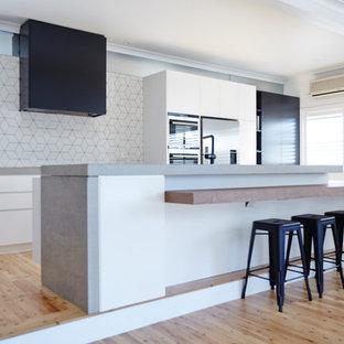 Foto di una cucina design di medie dimensioni con lavello sottopiano, ante lisce, ante nere, top in cemento, paraspruzzi bianco, paraspruzzi con piastrelle in ceramica, elettrodomestici in acciaio inossidabile, parquet chiaro e isola